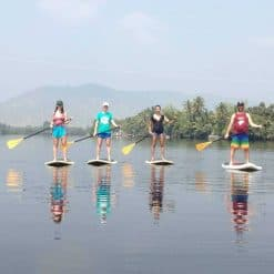 Four backpackers on stand up paddleboards on the Kampot river