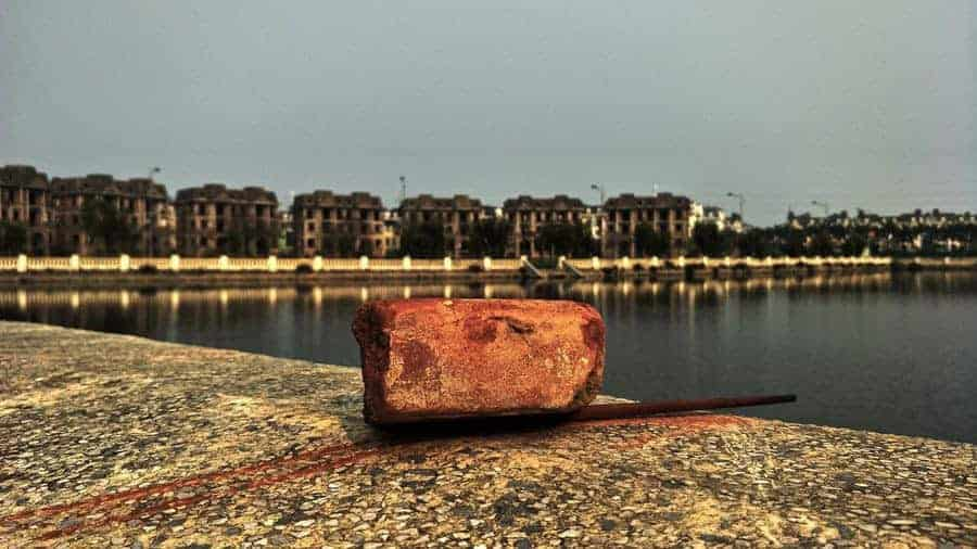 A brick in the foreground, a view over a lake, abandoned buildings in the background.
