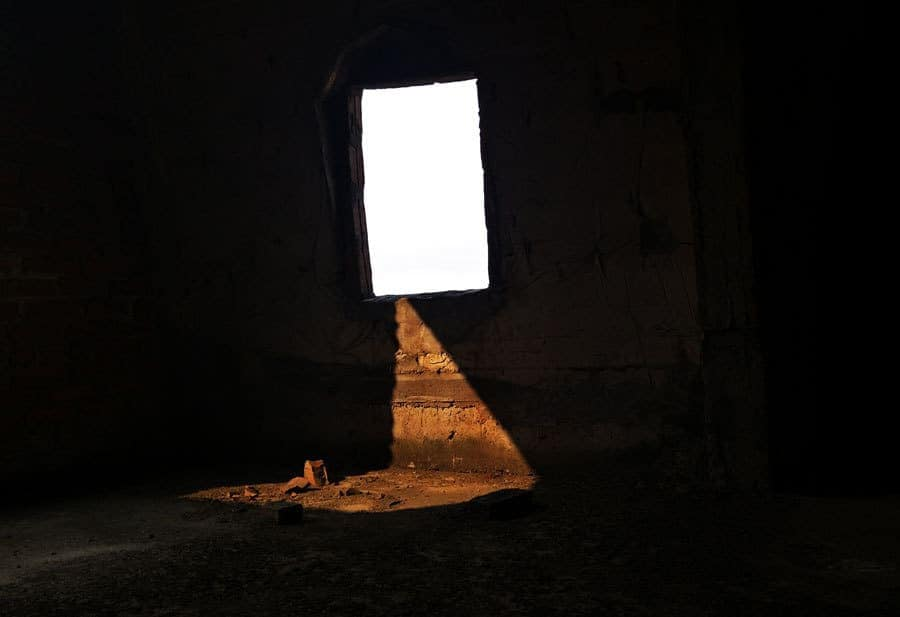 Light shines through a window in an abandoned building.