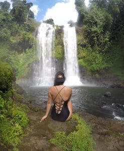 A girl in a swimsuit sits with her back to the camera by a waterfall