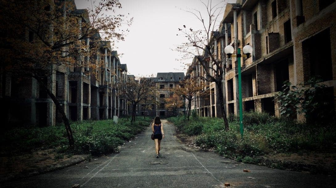 Nikki walks down the road between two rows of half built houses in Lideco Bac 32, Hanoi