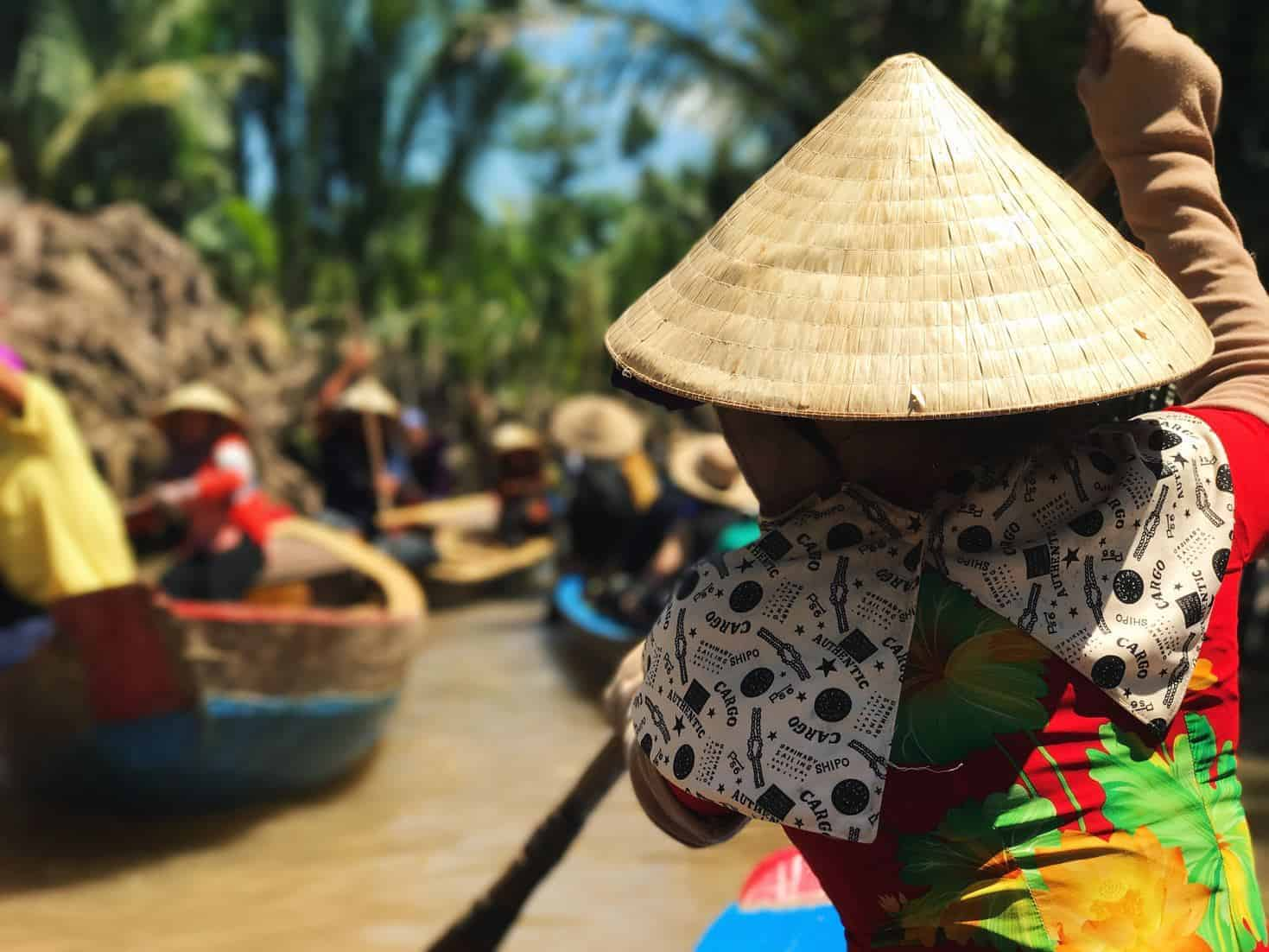 A Vietnamese lady rows towards other boats on the Mekong River. Photo by Anne Lin on Unsplash