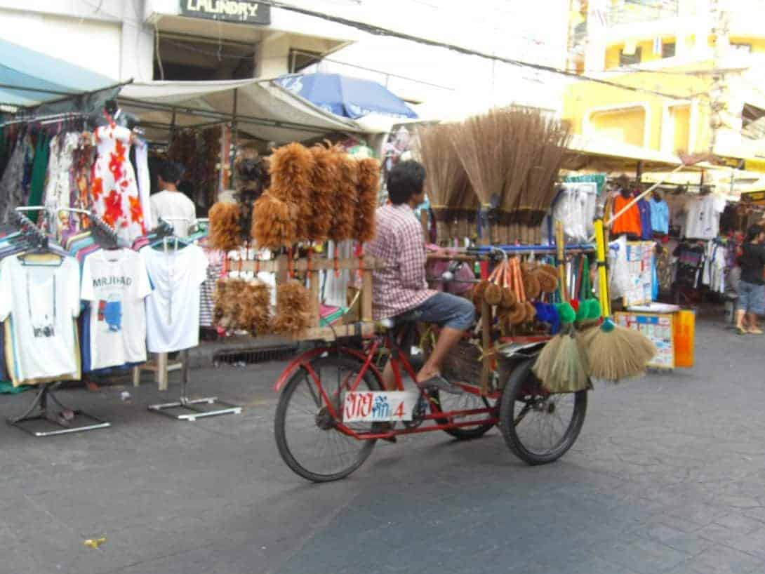 "A local man ""pedals"" brushes down the Khao San Road."