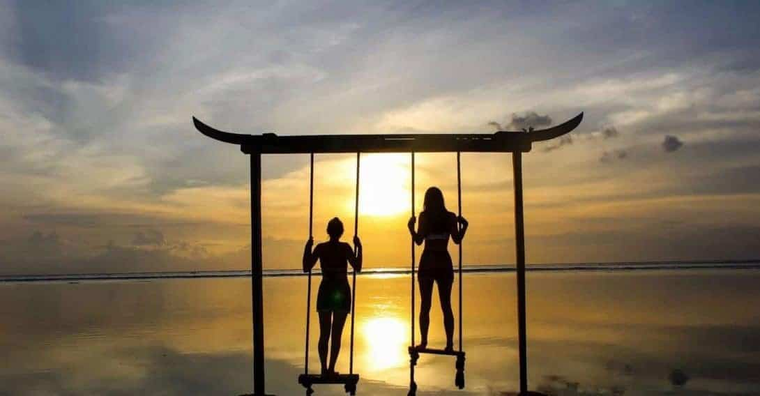 The Silhouette of Two Girls Standing on a Swing During Sunset on Gili Trawangan
