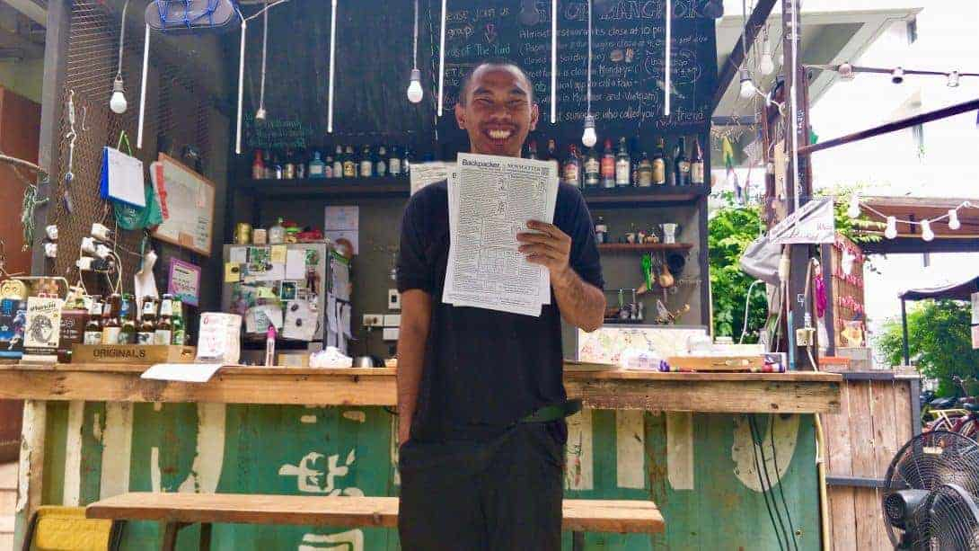 Staff member holds SEA Backpacker Newsletter at The Yard Hostel, Bangkok