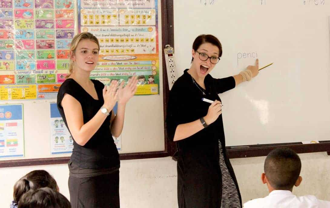 Two girls teach English in a classroom in Thailand