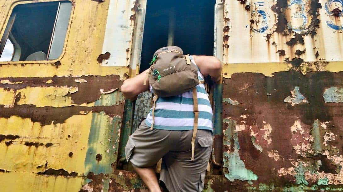 Climbing onto an abandoned train in Bangkok.