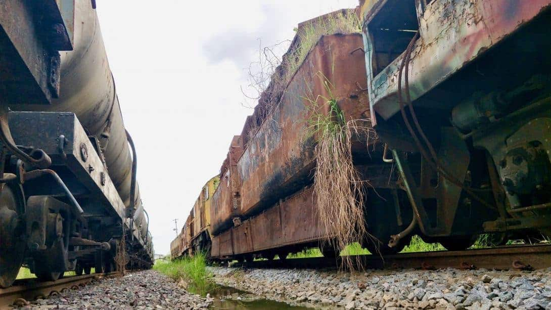 Grass and plants grow out of old rusty train carriages in Bangkok, Thailand.