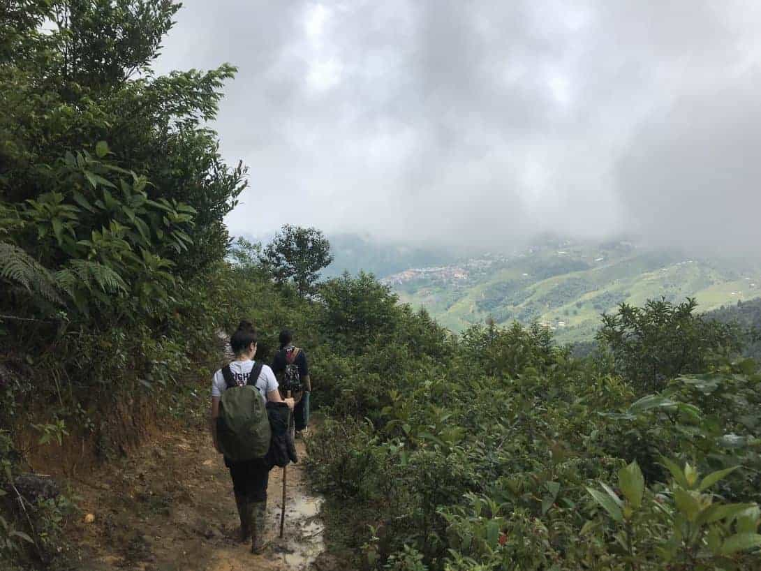 Two Girls Walk Along A Path With Muddy Ground During A Sapa Trek