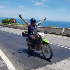 A Man Rides a Bike With Both Arms in the Air on the Hai Van Pass, Vietnam