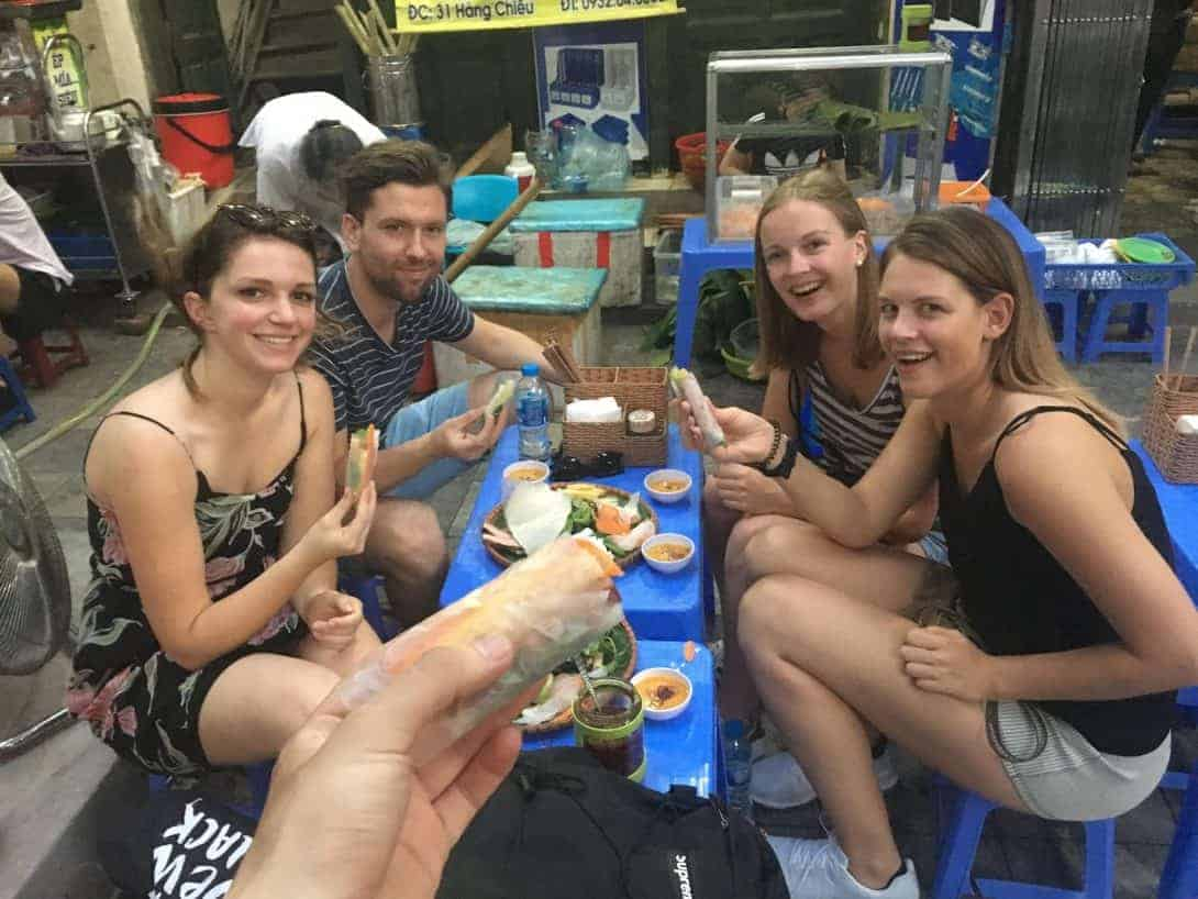 Eating fresh spring rolls on a Hanoi street food tour.