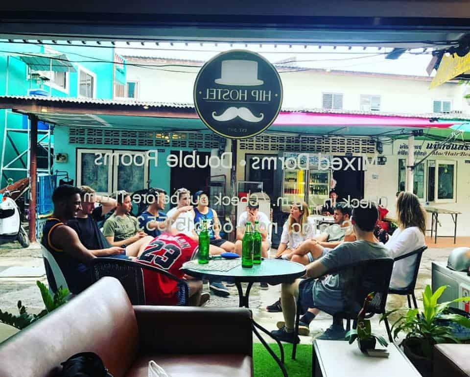 Backpackers enjoying their drinks as they catch up with each other at Hip Hostel, Phuket, Thailand.