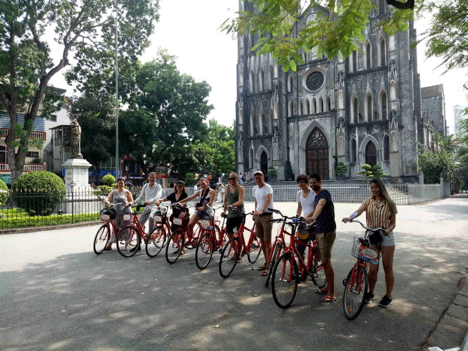 A Group Of Backpackers Pose With Their Bikes In Front Of Saint Joseph's Cathedral in Hanoi.