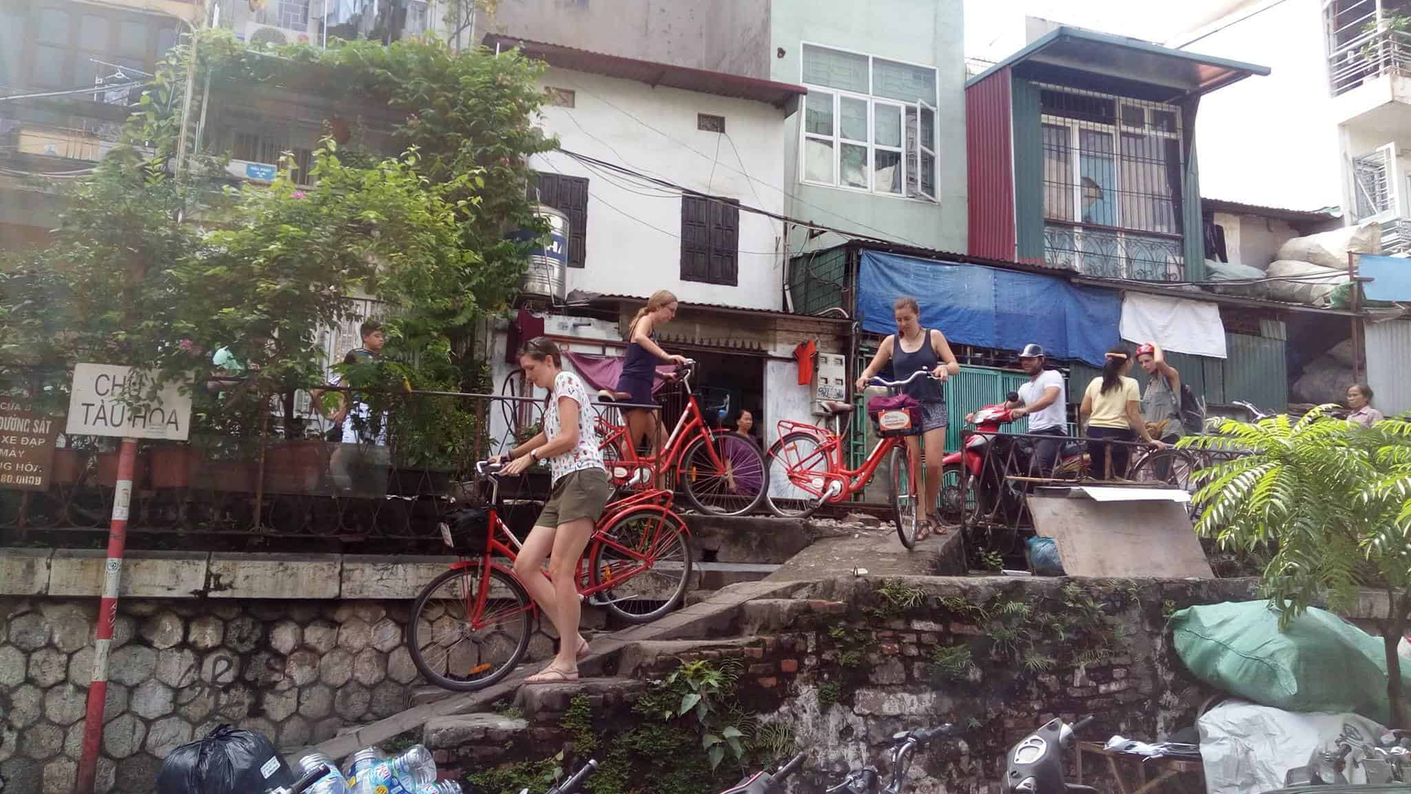 A Group Of Travellers Push Their Bikes Down a Ramp in Hanoi During Their Cycling Tour.