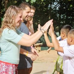backpackers hi fives to local kids - Mae Wang, Thailand
