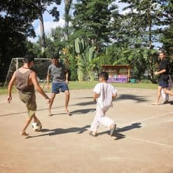 backpackers playing soccer with children - Mae Wang, Thailand