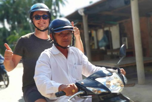 Riding pillion with an experienced local driver on the Mekong Madness Tour!
