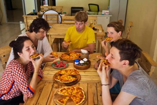 Backpackers eating pizza_CocoHostel_Khao Sok Thailand