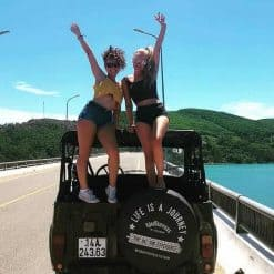 Two Girls Stand on a Jeep