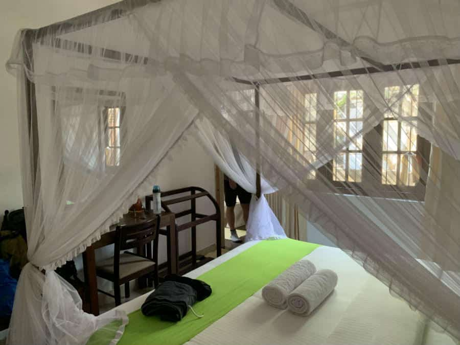 A Very Clean Room With Mosquito Nets Over The Bed
