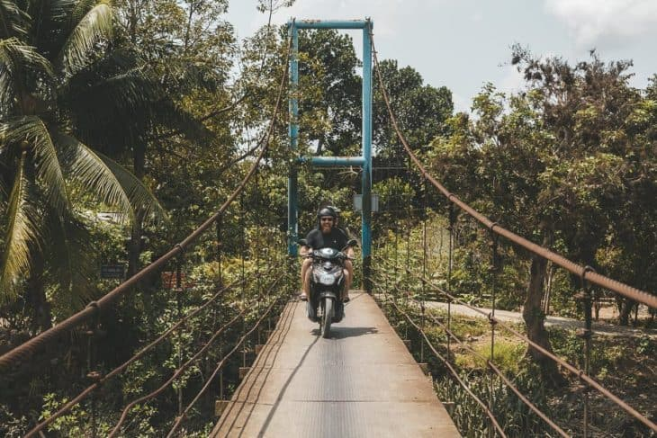 A Couple Cross A Metal Bridge in the Mekong Delta on a Bike Tour