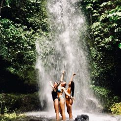 Girls standing at the bottom of a waterfall on Lombok.