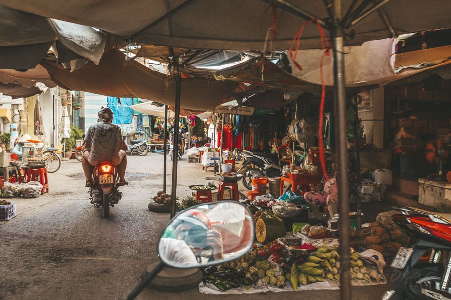 A Traveller Rides on a Scooter Through a Local Market in Vietnam