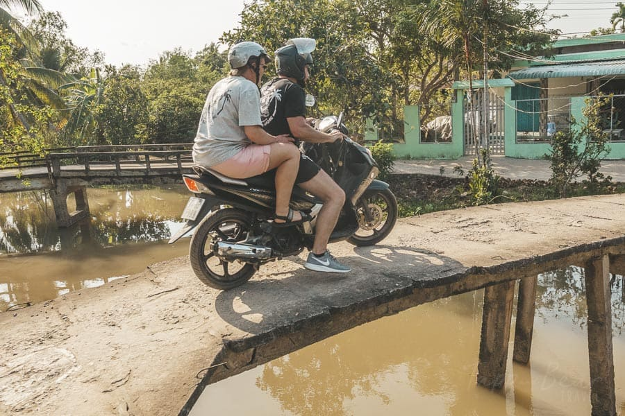 A Couple Cross A Wooden Bridge on a Moped