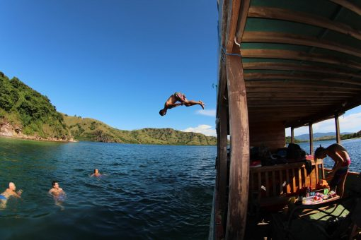 A Traveller Dives Off The Top of a Boat in Komodo, Indonesia