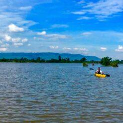 Person kayaking on beautiful Trav Kot Lake, Cambodia