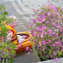 Man in kayak smiles from behind flowers