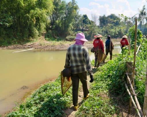 People walk alongside river