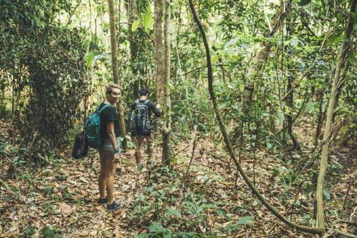 Girl turns around trekking in jungle