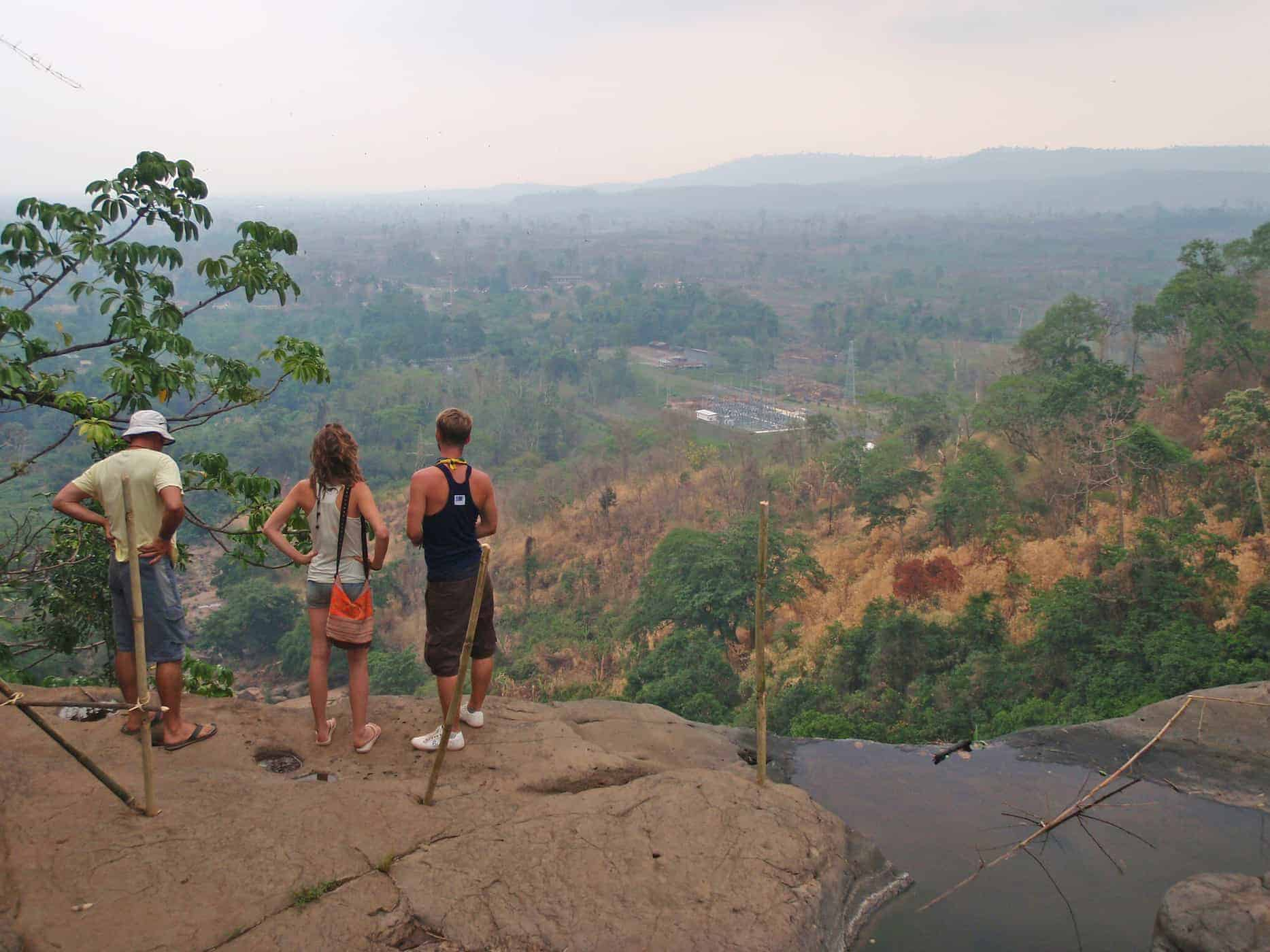 Tadlo, Bolaven Plateau, Laos. Travellers stand on a rock.