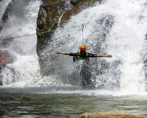 Man with arms spread in front of waterfall