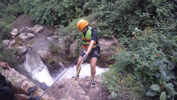 Girl abseils down rock face over waterfall