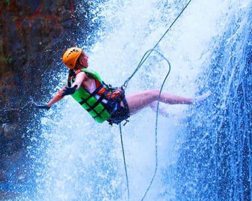 Girl rapelling down waterfalll