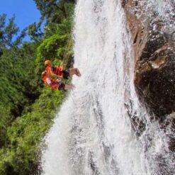 Abseiling down high waterfall