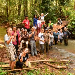 Volunteers pose near bridge