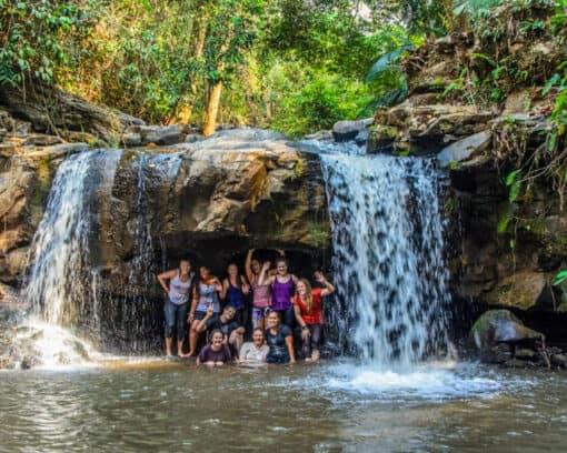 Volunteers under jungle waterfall