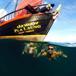 People swimming under water near Thai junk boat.