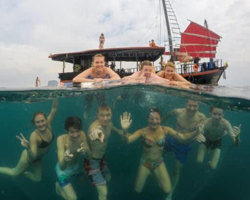 Backpackers smiling underwater near Junk Boat.