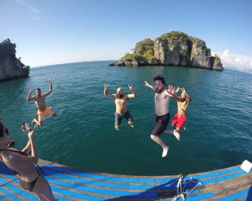 Guys jumping off boat close to Thai island.