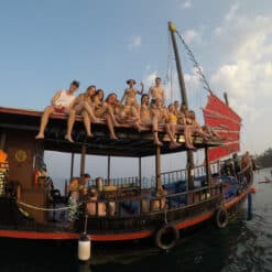 Backpackers on top of junk boat.