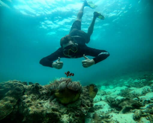 Man snorkels and poses next to fish in Thailand.