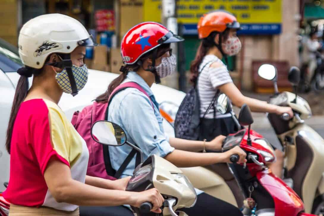 Locals wearing masks while riding motorbikes in Southeast Asia.