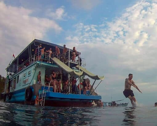 Oxygen tour boat with man jumping.