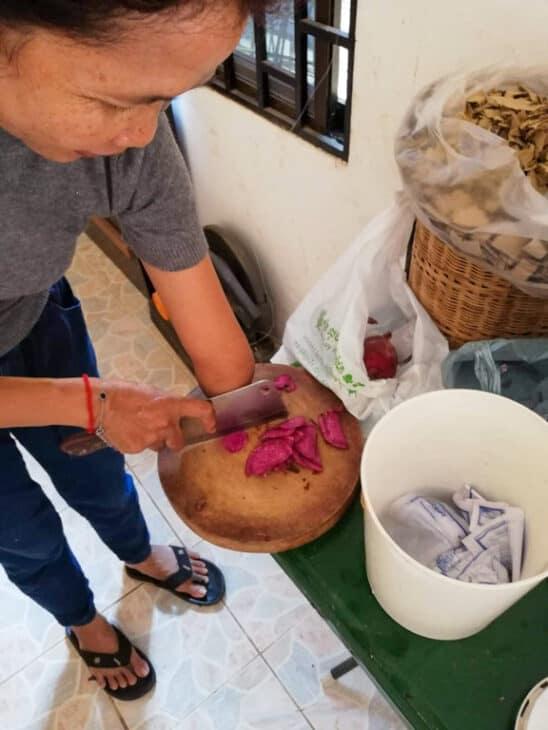 Woman cuts yams.