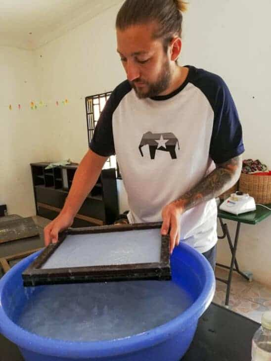 Man making paper in frame.