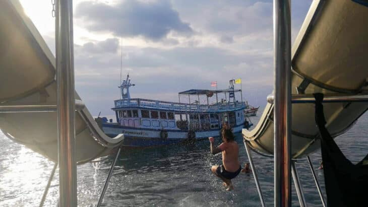 People slide down water slides off back of boat in Thailand.